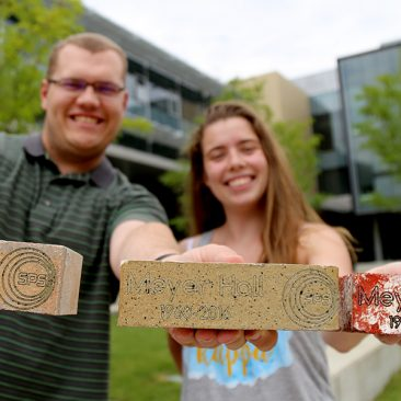 Students holding Meyer Hall bricks